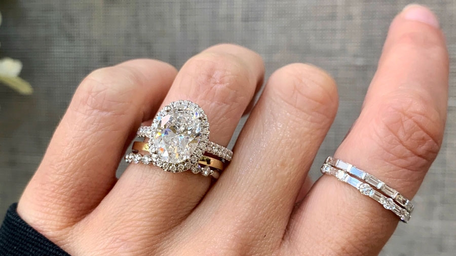 Wedding Rings and Oval Engagement Ring on Hand